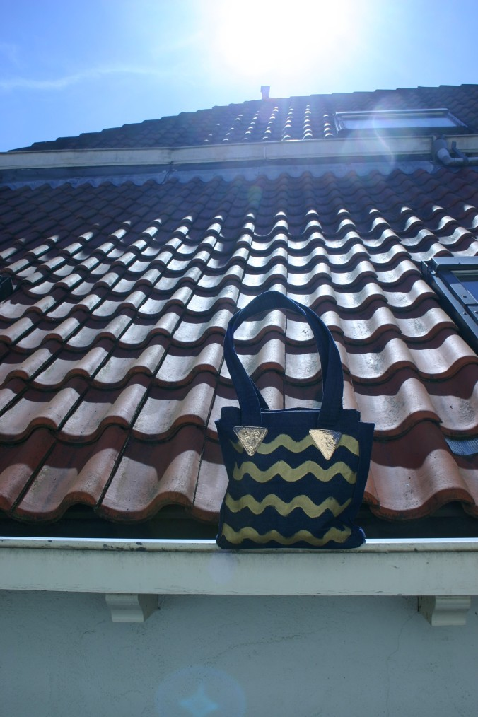 diy denim bag with painted gold colored waves on the rooftops in Kloksteeg Delft Netherlands
