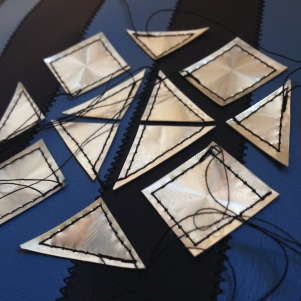 sewing holographic vinyl triangles to decorate the bag