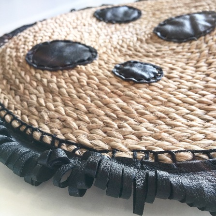 round leather decorations attached to a straw bag